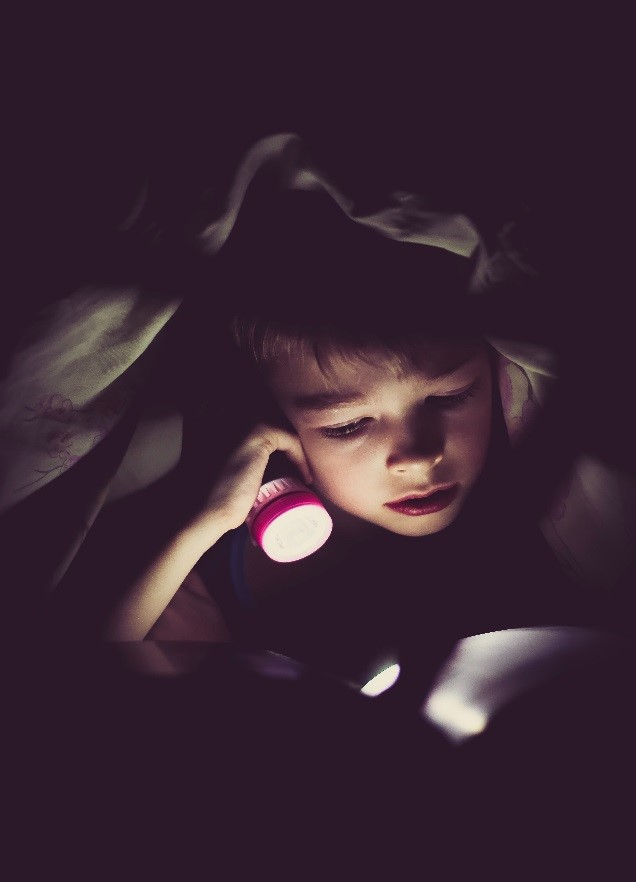 Child  Reading with Flashlight.